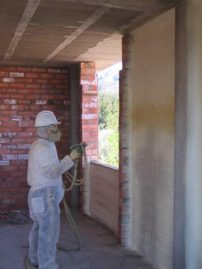 Aplicador de poliuretano proyectado aislando la fachada por el interior.
